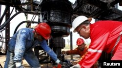 FILE - Men work at an oil pump in Lagunillas, Ciudad Ojeda, in the state of Zulia, Venezuela, March 20, 2015.