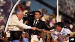 Un devoto estira su mano para tocar la mano del Papa a su arribo a la misa en Colombo.