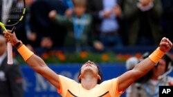 Rafael Nadal merayakan kemenangannya atas Fabio Fognini dari Italia dalam turnamen Barcelona Terbuka (22/4). (AP/Manu Fernandez)