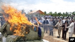 "Cambodian officers burn some three tones of various drugs are seized in the nation wide of this country at the outskirt of Phnom Penh, Cambodia, Tuesday, June 2, 2009. Cambodian authorities torched nearly 3 tons of herbs used to produce ""herbal ecstasy"" a"