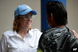 Mayor Carmen Yulin Cruz speaks with a man as she arrives at a hospital in the Rio Piedras area of San Juan, Puerto Rico, Sept. 30, 2017.