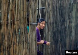 FILE - A refugee who fled Myanmar watches from behind a bamboo wall of a stilt house as Thai authorities conduct a census at Mae La refugee camp, near the Thailand-Myanmar border in Mae Sot district, Tak province, Thailand. Many refugees are hopeful about