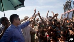 A Bangladeshi officer tries to calm Rohingya refugees during a protest against repatriation at Unchiprang refugee camp near Cox's Bazar, in Bangladesh, Thursday, Nov. 15, 2018. (AP Photo/Dar Yasin)