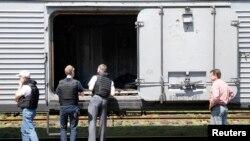 Chuyên gia của Tổ chức An ninh và Hợp tác châu Âu kiểm tra một toa xe đông lạnh chứa đựng thi thể các nạn nhân của chuyến bay MH17 bị bắn rơi tại một nhà ga ở thị trấn Torez, vùng Donetsk, ngày 20/7/2014.