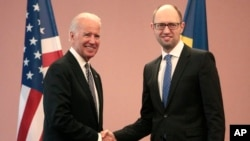 U.S. Vice President Joe Biden, left, shakes hands with Ukrainian Prime Minister Arseniy Yatsenyuk during a meeting in Ukraine. (April. 22, 2014.)