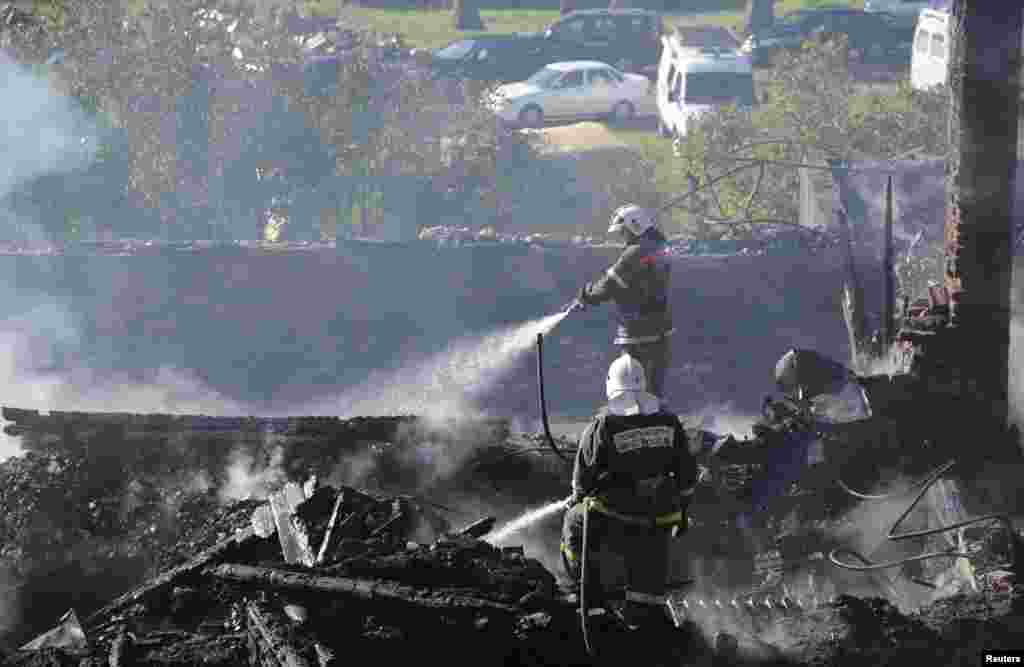 Firefighters work amidst the debris of a psychiatric hospital destroyed by fire in the Novgorod region town of Luka, Sept. 13, 2013.