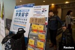 Seorang mahasiswa China berbicara di telepon di belakang poster iklan pendidikan luar negeri usai ujian SAT (Scholastic Assessment Test) di AsiaWorld-Expo, Hong Kong, 2 November 2013. SAT adalah pra syarat mendaftar ke perguruan tinggi AS. (Foto: Reuters)