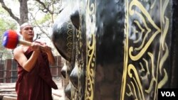 A Myanmar monk ringing a giant gong. (Z. Aung/VOA)