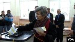 Žena ubacuje dva listića na jednom od tri biračka mesta na kojima su izbori ponovo održani