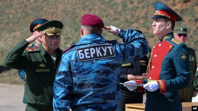 "A photo provided by the Russian Defense Ministry shows Russian Defense Minister Sergei Shoigu (L) awarding a former Ukrainian special forces ""Berkut"" officer (back to camera) at a military base in Sevastopol, Crimea, March 24, 2014."