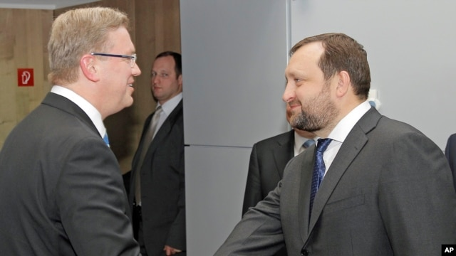 European Commissioner for Enlargement and European Neighborhood Policy Stefan Fuele (l) and Serhiy Arbuzov, Ukrainian Deputy Prime Minister, at the European Commission headquarters in Brussels, Dec. 12, 2013.