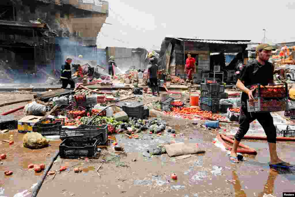 People gather at the site of a car bomb attack in Jamila market in Sadr City district of Baghdad, Iraq.