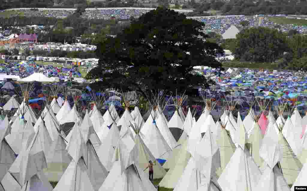 A festival goer erects tipis at Worthy Farm in Somerset during the first day of the Glastonbury Festival, Britain.