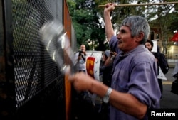 A demonstrator hits a police fence during a protest against the visit by U.S. President Barack Obama to Argentina, outside the U.S. Embassy in Buenos Aires, March 23, 2016.