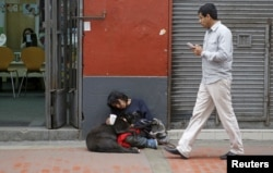 Arturo Tello sleeps with his dog, Negrita Rubi, as he asks for money in downtown Lima, Sept. 23, 2015.