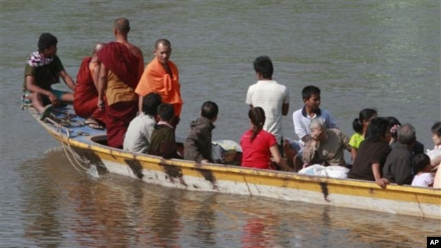 A boat carrying last batch of Burmese refugees back home cruises on the Moei river in Mae Sot, Thailand, 10 Nov 2010