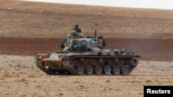 FILE - A Turkish army tank takes up position on the Turkish-Syrian border near the southeastern town of Suruc in Sanliurfa province, Sept. 29, 2014.