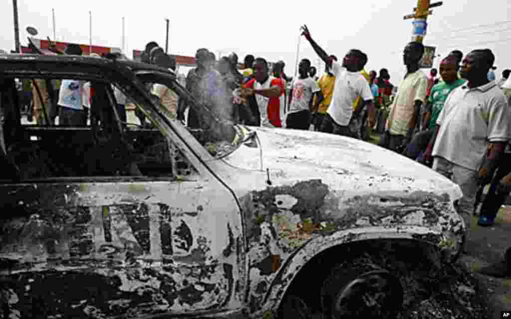 Ivorian students protest near a burnt U.N. vehicle during a demonstration at the junction of Riviera 2 in Abidjan, 13 Jan 2011.