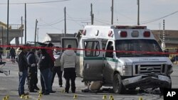 Forensic experts work on the scene after unknown gunmen opened fire on an ambulance, killing the driver, two patients and a relative of one of the patients in the northern border city of Ciudad Juarez, Mexico, December 7, 2011.