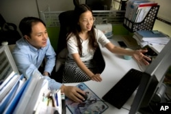 FILE - He Jiankui, left, and Zhou Xiaoqin work a computer at a laboratory in Shenzhen in southern China's Guangdong province, Oct. 10, 2018. Chinese scientist He says he helped make the world's first genetically edited babies.