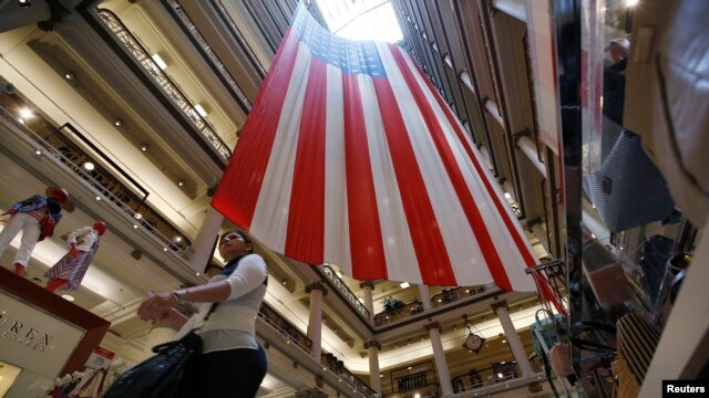 A shopper walks past a 100-foot U.S. flag that will be on display to honor veterans until July 4th, in a department store in Chicago, Illinois, May 23, 2014.
