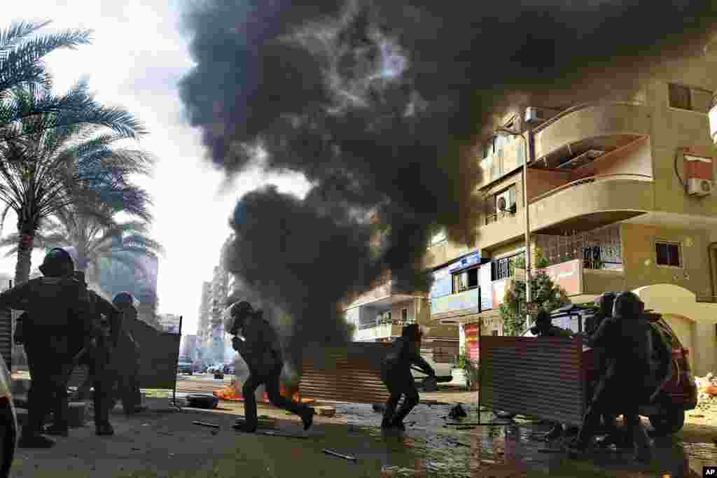 Egyptian security forces clash with supporters of ousted President Mohamed Morsi in the Nasr City district of Cairo. Hundreds of Islamists rallied in Cairo and across the country, calling for a boycott of an upcoming constitutional referendum.