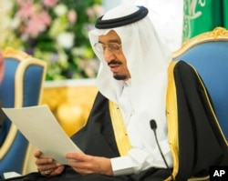In this photo provided by the Saudi Press Agency, Saudi King Salman delivers his first major policy speech since assuming the throne in the al-Yamama palace, Riyadh, Saudi Arabia, March 10, 2015.