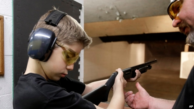 FILE - An instructor shows a boy, 12, how to hold a shotgun at a shooting range in Houston, Texas, May 19, 2013.