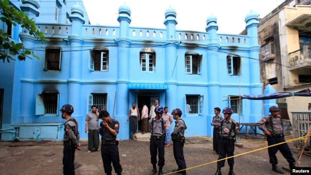 Police stand in front of a mosque and school dormitory that were damaged by a fire in Rangoon, Burma, April 2, 2013.