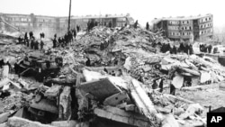 Teams of workers climb over rubble left by the earthquake. Leninakan, Armenia, Dec. 12, 1988.