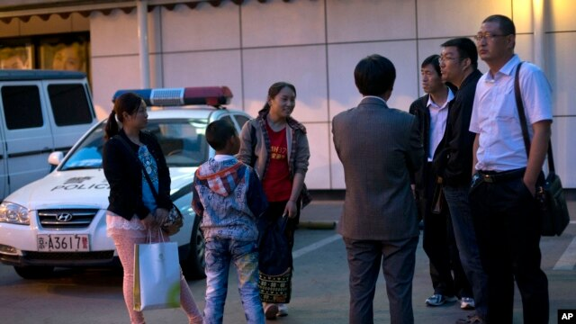 Relatives of Chinese passengers onboard the missing Malaysia Airlines Flight 370, left, talk to Chinese officials, right, outside a hotel as the Malaysia Airlines ceased to provide the hotel accommodation for the relatives in Beijing Friday, May 2, 2014