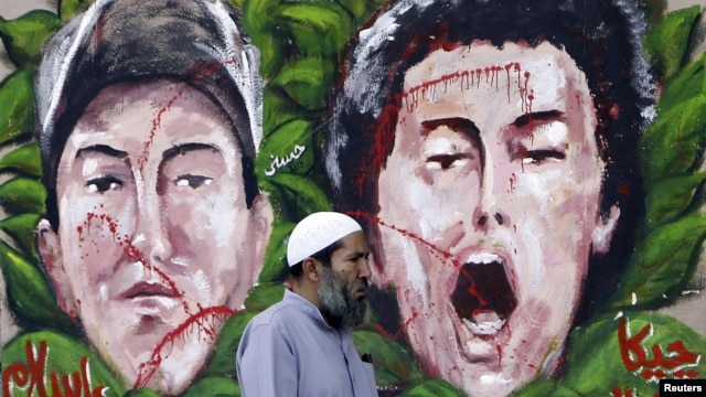 An anti-Mursi protester walks past graffiti depicting two activists who died recently, at Tahrir Square in Cairo December 10, 2012.
