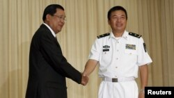 Yu Manjiang (R), commander officer of the Chinese fleet, is welcome by Cambodia's Prime Minister Hun Sen in Phnom Penh, Feb. 24, 2016.