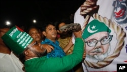 A Bangladeshi man throws a shoe at a Motiur Rahman Nizami poster to celebrate the execution of the Jamaat-e-Islami party's senior leader outside Dhaka's central jail, Bangladesh, early Wednesday, May 11, 2016.