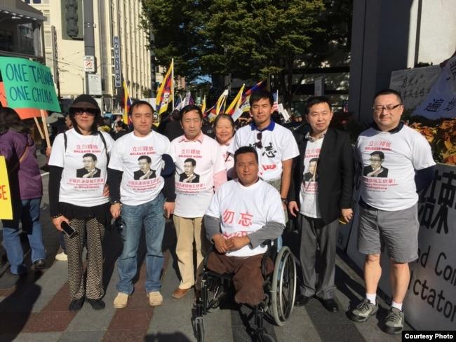 2015年9月,王在刚在西雅图参加抗议习近平的活动,为六四残疾人士方政推轮椅(王在刚提供)