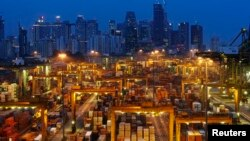 The skyline of Singapore's central business district is seen at dusk as operations continue at a PSA International port terminal in Singapore September 25, 2013. Connected to more than 600 ports in some 120 countries, Singapore is one of the world's busie