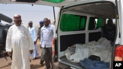 Ibrahim Gaidam, Governor of Yobe state, left, looks at bodies of students inside an ambulance outside a mosque in Damaturu, Nigeria, Tuesday, Feb. 25, 2014. Islamic militants killed dozens of students in a pre-dawn attack Tuesday on a northeast Niger