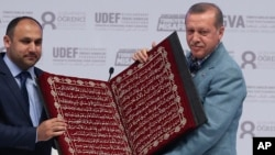 Turkey's President Recep Tayyip Erdogan (R) receives a copy of the Quran, Islam's holy book, at an international students meeting in Istanbul May 16, 2015.