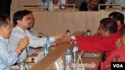 PM Abhisit Vejjajiva berjabat tangan dengan pemimpin demonstran Veera Musikapong dalam pertemuan di Bangkok, 28 Maret 2010.