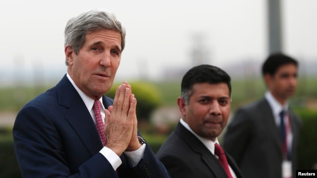 U.S. Secretary of State John Kerry greets the media upon his arrival at the airport in New Delhi July 30, 2014.