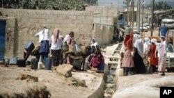 Des réfugiés puisent de l'eau dans un camp en Jordanie