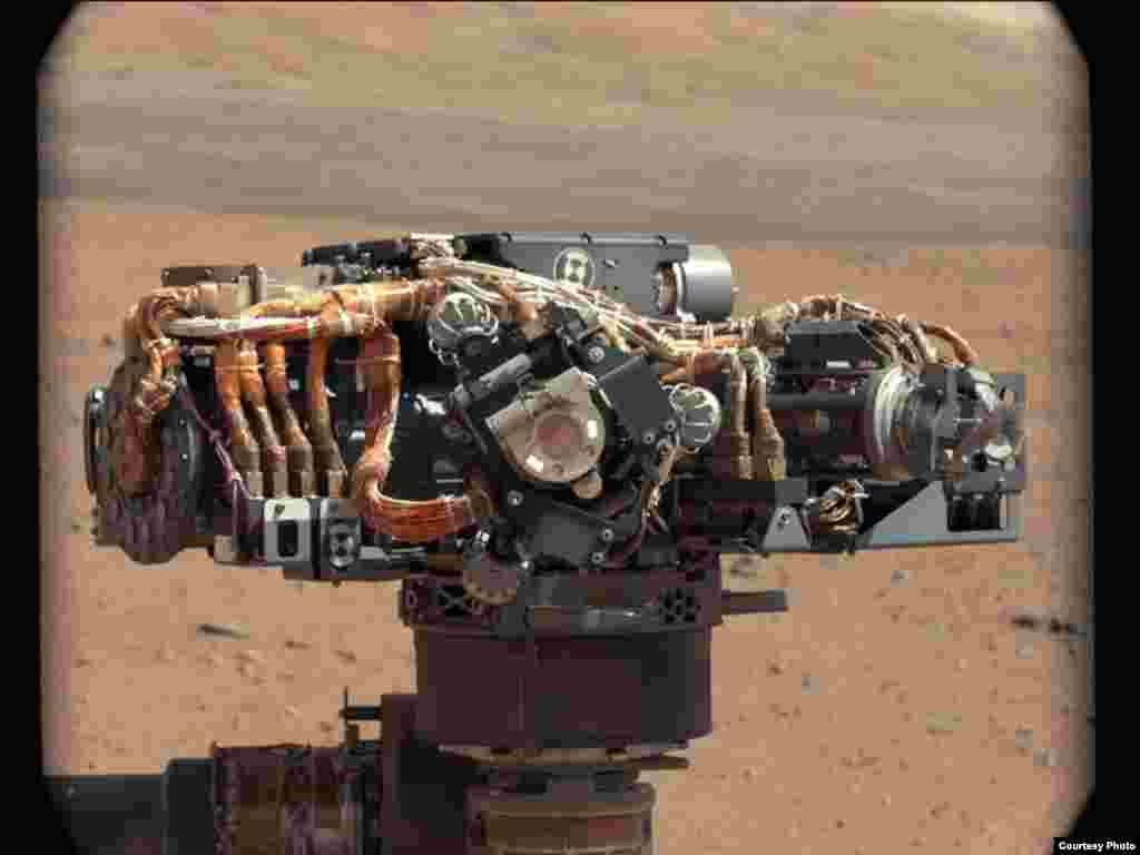 Máy chụp ảnh của xe Curisosity, với quang cảnh sao Hỏa phía sau.