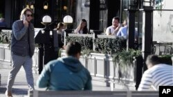 People sit in an outdoor restaurant area in Christchurch, New Zealand, Monday, June 8, 2020. New Zealand appears to have completely eradicated the coronavirus, at least for now. (AP Photo/Mark Baker)
