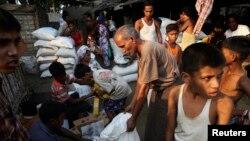 Warga Rohingya berbagi bantuan makanan dari World Food Program di kam Thae Chaung di Sittwe, Rakhine, 2014. (Foto: Dok)