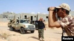 Un combattant des forces loyales au gouvernement d'union nationale de la Libye surveille les positions occupées par le groupe Etat islamique dans la zone d'Algharbiyat à Syrte, le 21 juin 2016.