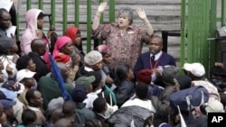 FILE: An immigration official addresses Zimbabweans outside an immigration office in downtown Johannesburg, South Africa, December 15, 2010, as they attempt to become legal.