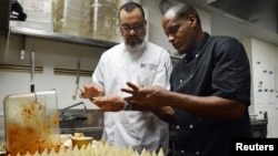 Executive chef Miguel Aguilar (L) shows chef Michael Alejandro Calvo Oviedo of El Atelier restaurant in Havana, Cuba, how to make chicken ropa vieja empanadas at Wynwood Kitchen & Bar in Miami, Florida, Aug. 13, 2015.