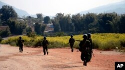 FILE - Myanmar army soldiers patrol a road in Feb. 2015 as part of operations against ethnic rebels in Kokang, northeastern Shan State, Myanmar.