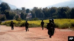 FILE - Myanmar army soldiers carrying weapons patrol on a road as part of operations against ethnic rebels, in Kokang, northeastern Shan State, more than 800 kilometers (500 miles) northeast of Yangon, Feb. 17, 2015.