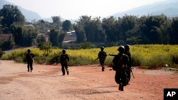 FILE - Myanmar army soldiers carrying weapons patrol on a road as part of operations against ethnic rebels, in Kokang, northeastern Shan State, more than 800 kilometers (500 miles) northeast of Yangon, Myanmar.